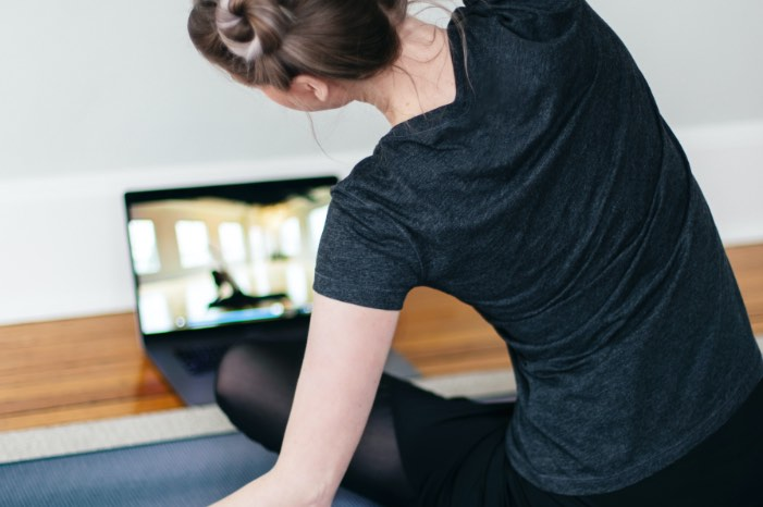 Woman streching in front of laptop
