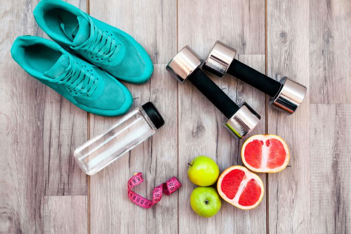 Shoes, weights, water bottle, and fruit laying on wood floor