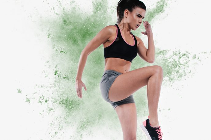 Plant-based fitness! Exciting photo of woman high-stepping in front of exploding plant protein powder