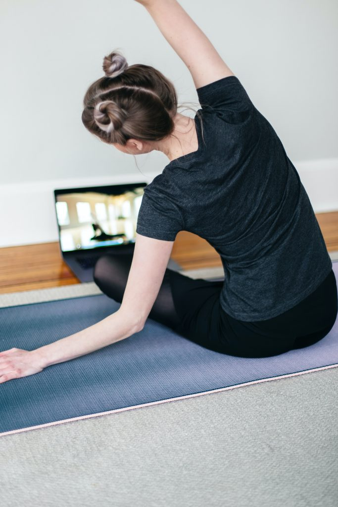 a woman doing yoga online with an online fitness coach