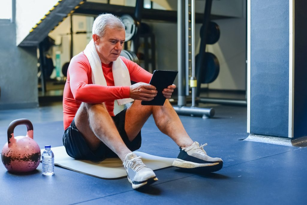 man using his tablet with a fitness app to help him exercise