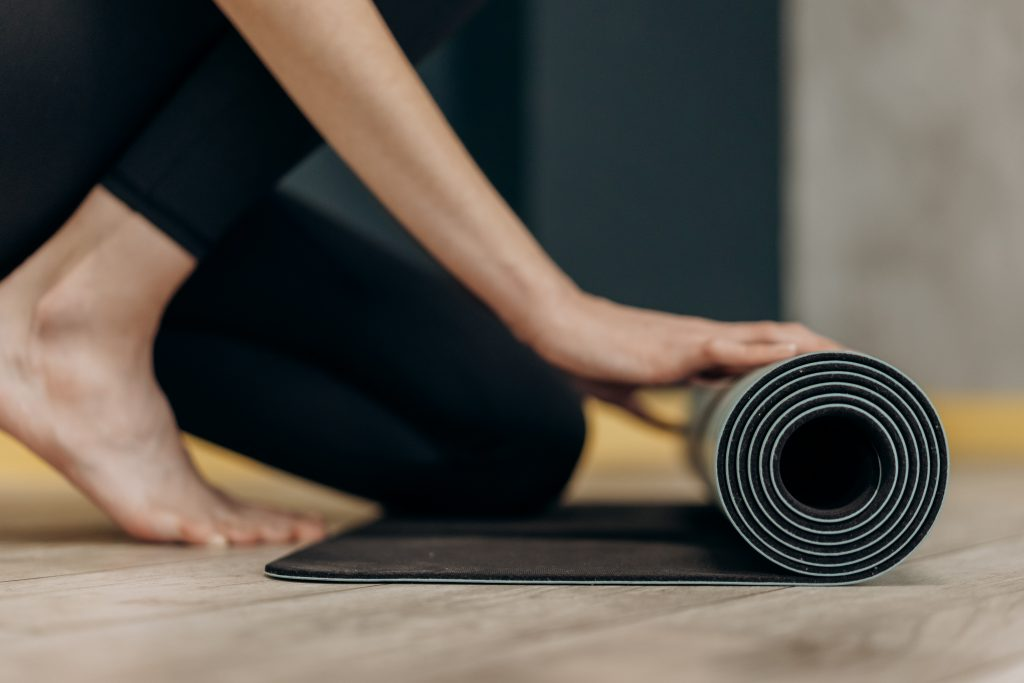 woman rolling up a yoga mat ready to do her fitness
